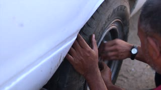Changing a wheel in an old pickup truck. Repair of car on the road. Broken in the old car.