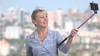 Charming mature woman using selfie stick. Beautiful business lady taking selfie with monopod on blurred background.