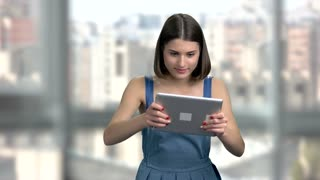 Charming woman playing on pc tablet. Excited woman playing game on computer tablet, blurred background. People, technology, fun.