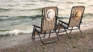 Checkered deck chairs on the sandy beach. Romantic summer vacation on seashore.