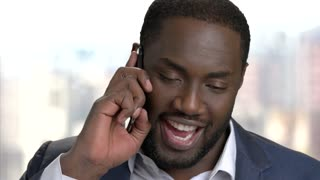 Cheerful afro-american entrepreneur talking on phone. Smiling african-american businessman talking on cell phone close up.