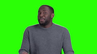 Cheerful afro-american guy on green screen. Handsome smiling dark-skinned man is dancing and looking at camera on Alpha Channel background.