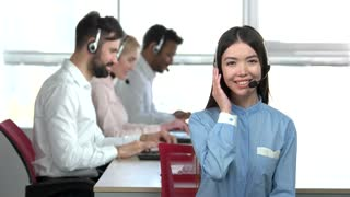 Cheerful asian girl in call center with headset agreeing. Adorable japaneese girl in office, colleagues background.
