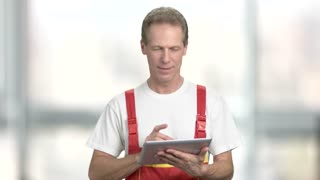 Cheerful builder using pc tablet. Smiling engineer working on digital tablet and looking at camera, blurred background.