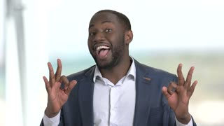 Cheerful businessman showing different gestures. Afro-american businessman demonstrating different gestures and facial expressions on blurred background.