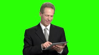 Cheerful businessman using tablet. Smiling mature man in suit swiping tablet.