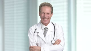 Cheerful doctor on blurred background. Mature male doctor with stethoscope laughing and at hospital.