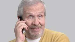 Cheerful elderly man with phone. Older man talking on mobile phone close up, grey background.