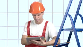 Cheerful engineer using pc tablet. Smart and modern builder using wireless tablet, window background.