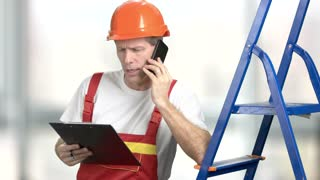 Cheerful foreman talking on cell phone. Smiling construction engineer looking at clipboard and talking on mobile phone, blurred background.