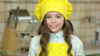 Cheerful girl in chef uniform. Child showing thumb up. How to cook good food.