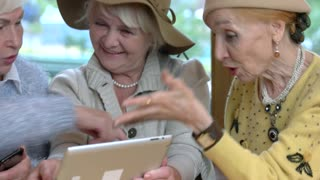 Cheerful ladies with a tablet. Senior women laughing and talking.