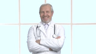 Cheerful male doctor with arms crossed. Smiling senior doctor on clinic window background, portrait. Face of happy doctor.
