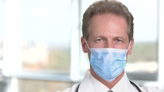 Cheerful mature male doctor in protective mask. Physician smiling in medical protective mask on abstract blurred background in bright room in hospital.