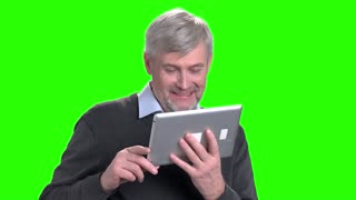 Cheerful middle-aged man talking via pc tablet. Happy grandfather using digital tablet on green screen background.