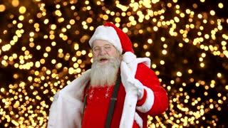 Cheerful Santa Claus dancing. Santa on lights background.