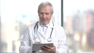 Cheerful senior doctor using digital tablet. Elderly male doctor in white coat texting a message on blurred background.