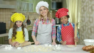 Cheerful woman and kids, kitchen. Smiling people showing thumbs up. Free cooking classes.