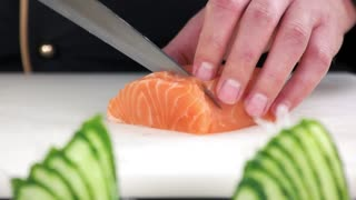 Chef cutting salmon close up. Sliced raw fish.
