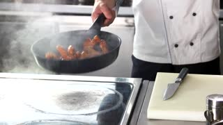 Chef frying chicken wings. Meat being cooked.