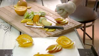 Chef hand processing apple slices with lemon juice. Assortment of cutted fruits on wooden board. Cooking cake at restaurant.