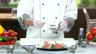Chef pouring sauce on salad. Food preparation, cooking table.
