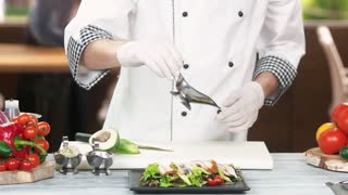 Chef preparing salad, sauce. Tasty dish on kitchen table.