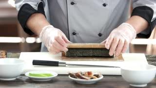 Chef shaping a sushi roll. Japanese food preparation, bamboo mat.