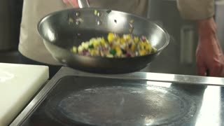Chef Tossing Food In Pan, slow-mo. Close up chef hands tossing chopped vegetables in the air above stove, slow-mo.