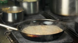 Chicken pasta in frying pan. Food being cooked, kitchen.