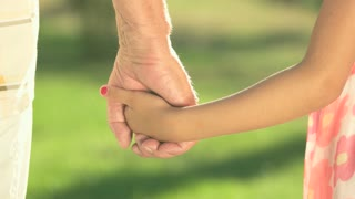 Child and grandfather holding hands. Little girl and senior man outdoors. Time spending together is priceless.