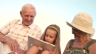 Child and grandparents using pc tablet. Loving grandparents and their little granddaughter using a digital tablet together outdoors. Young generation and modern technology.