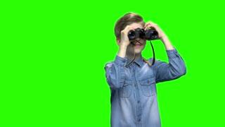 Child boy tourist looking through binoculars. Green hromakey background for keying.
