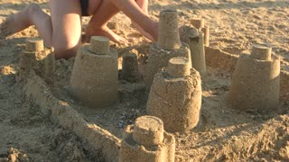 Child building sandcastle. Yellow beach sand and sunlight. Turn on your imagination.