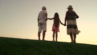 Child holding hands with grandparents, back view. Slow motion seniors with granddaughter standing on green lawn at sunset sky.