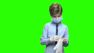 Child little boy puts on medical gloves. Wearing medical protective mask, role game. Green hromakey background for keying.