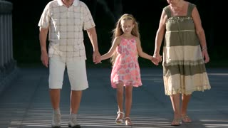 Child walking with her grandparents. Cute granddaughter holding hands with her grandparents on bridge. Happy family relationship.