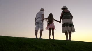 Child with grandparents is jumping, slow motion. Senior man and woman holding hands with granddaughter on evening sky background, back view. Beautiful leisure together.
