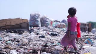 Children at the dump. Dispossessed orphans. Hungry children looking for food in a landfill.