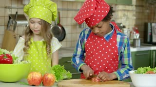 Children cooking food. Boy cutting lettuce.