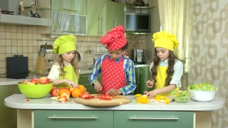 Children cutting vegetables. Fresh fruit on the table. Cooking school for kids.
