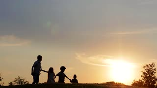 Children hold each other's hand on the background of beautiful sky. Kids walk at sunset.