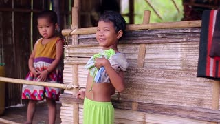 Children living in the jungle. Shy kids. Bamboo huts.