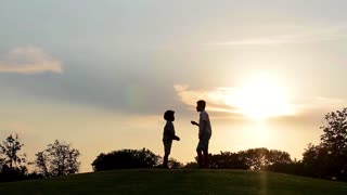Children playing at sunset. Kids run on the lawns of the evening.