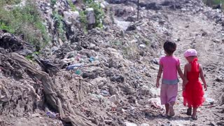 Children walk on the city dump. Children in poor areas. Two girls go through the trash. Third World countries.