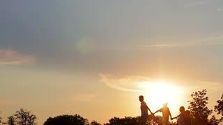 Children walking holding hands at sunset. Warm summer evening.