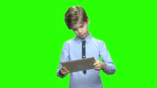 Children with tablet PC playing games. Boy holding modern gadget device and playing video games. Green hromakey background for keying.
