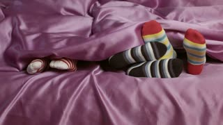 Children's feet in colorful socks. Kids on bed. Wear what you want to. Gentlemen woke up.