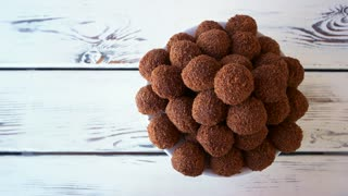 Chocolate ball shaped cookies. Sweets on wooden background, top view. Yummy dessert on table.