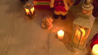 Christmas holiday candles and gifts. Burning lantern and Christmas decoration on wooden floor. Festive holiday scene.